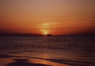 Sun behind fishing pier