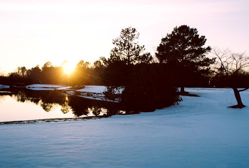Curvy snowy sunset over water